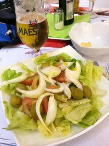 Salad with olive oil and salt in the background