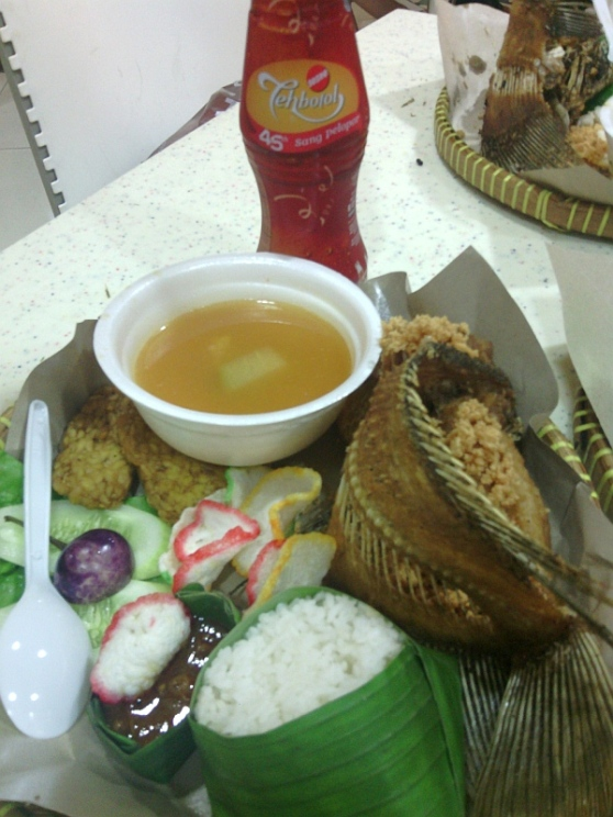 Ikan goreng with rice vegetables krupuk soup and Teh Botol