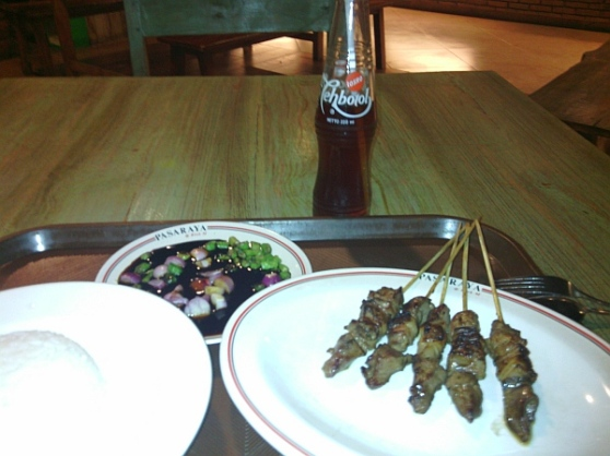 Sate with rice a sweet soya sauce ketchup dipping sauce and Teh Botol to drink